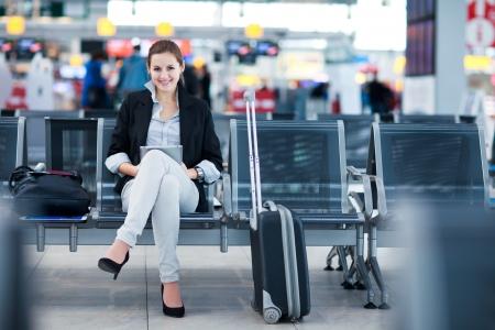 mujer con maleta: Pasajeros joven mujer en el aeropuerto, usando su Tablet PC a la espera de su vuelo (imagen a color entonado)