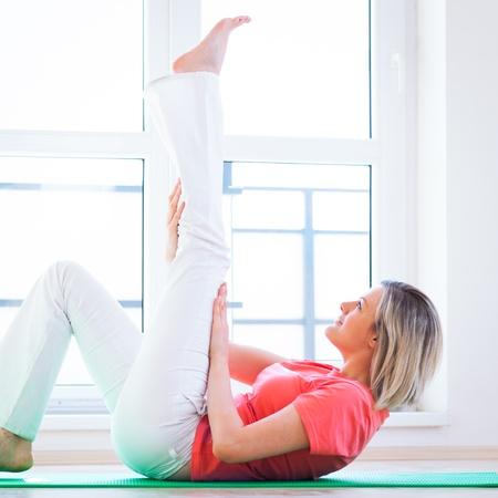 arrodillarse: Bastante joven haciendo ejercicio de yoga en casa