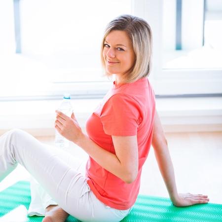 arrodillarse: Bastante joven refrescante durante el ejercicio en casa Foto de archivo