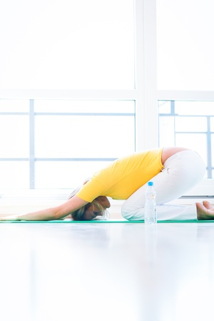 lying on back: Pretty young woman doing YOGA exercise at home