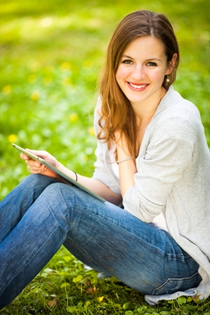 Young woman using her tablet computer while relaxing outdoors in a park on a lovely spring day Stock Photo - 14108958