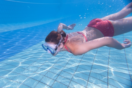summer wear: Underwater swimming: young woman swimming underwater in a pool, wearing a diving mask