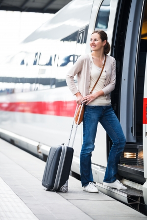 Pretty young woman boarding a train photo
