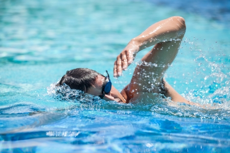 triathlon: Young man swimming the front crawl in a pool