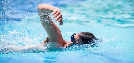 nuoto: Giovane nuoto il crawl in una piscina Archivio Fotografico