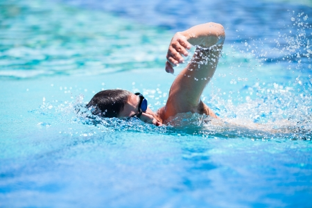 freestyle: Young man swimming the front crawl in a pool