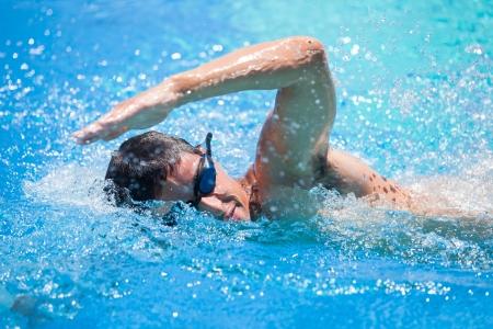 フロント クロール、プールで泳いでいる若い男