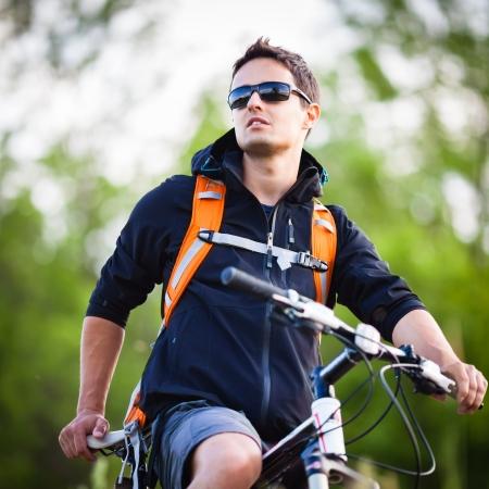 fitness hombres: Apuesto joven en bicicleta en el campo