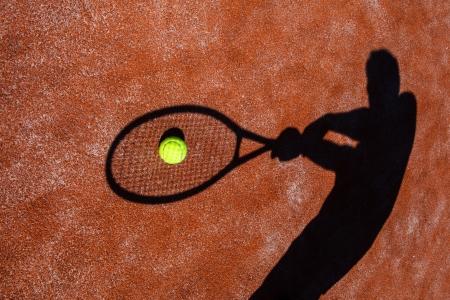tenis: sombra de un jugador de tenis en la acción en una pista de tenis Foto de archivo
