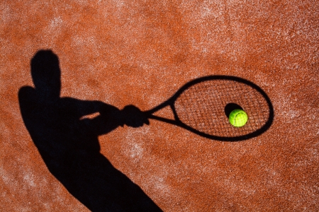 shadow of a tennis player in action on a tennis court  photo