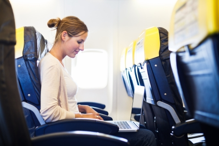 airplane girl: Young woman working on her laptop computer on board of an airplane during the flight
