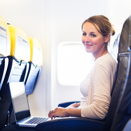 flight ticket: Young woman working on her laptop computer on board of an airplane during the flight