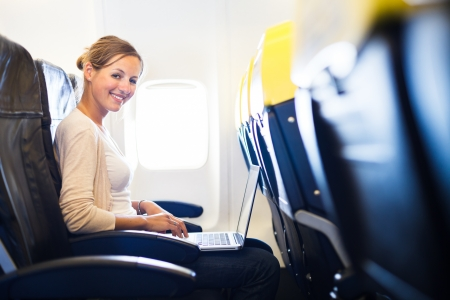Young woman working on her laptop computer on board of an airplane during the flight photo