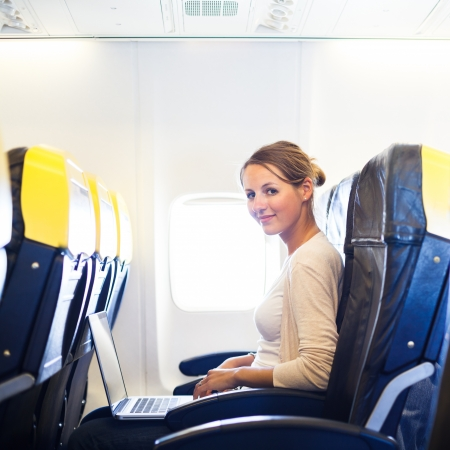 business trip: Young woman working on her laptop computer on board of an airplane during the flight