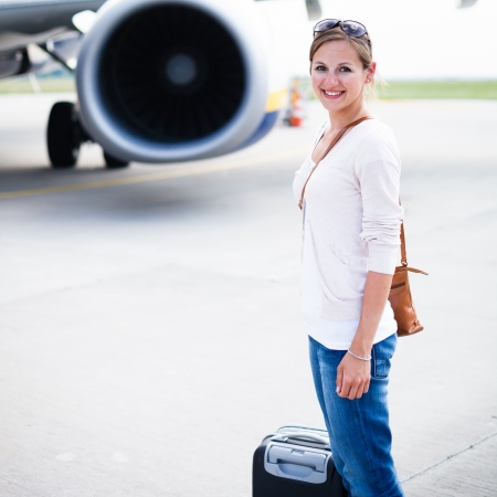 Just arrived: young woman at an airport having just left the aircraft photo