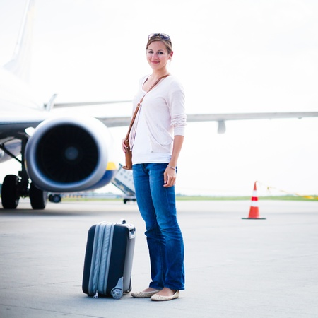 arrive: Just arrived: young woman at an airport having just left the aircraft