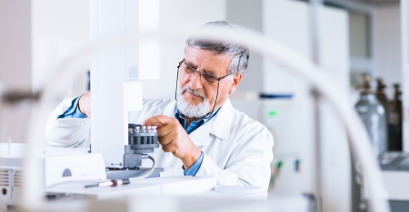 lab technician: senior male researcher carrying out scientific research in a lab using a gas chromatograph