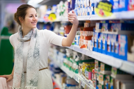 abarrotes: Joven y bella mujer de compras para los productos l�cteos en una tienda de alimentos  supermercado Foto de archivo