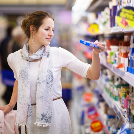 Beautiful young woman shopping for diary products at a grocery store/supermarket  photo