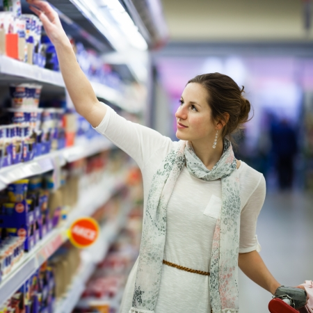 Beautiful young woman shopping for diary products at a grocery storesupermarket  photo