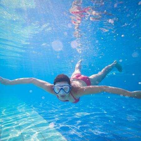 Onderwater zwemmen: jonge vrouw zwemmen onder water in een zwembad, het dragen van een duikbril