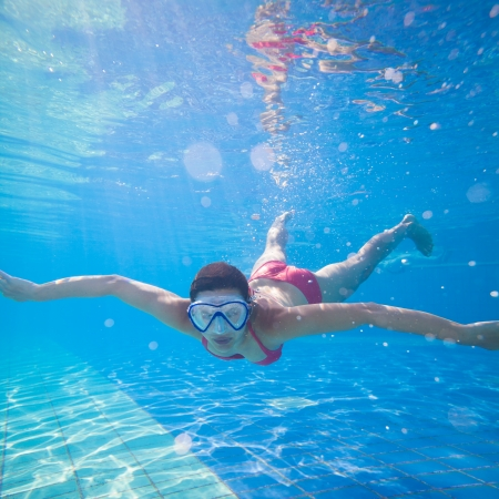woman diving: Underwater swimming: young woman swimming underwater in a pool, wearing a diving mask