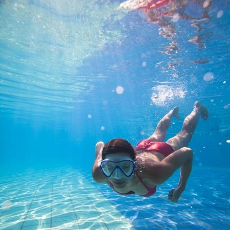 nadar: Nadar bajo el agua: mujer joven nadando bajo el agua en una piscina, con una m�scara de buceo