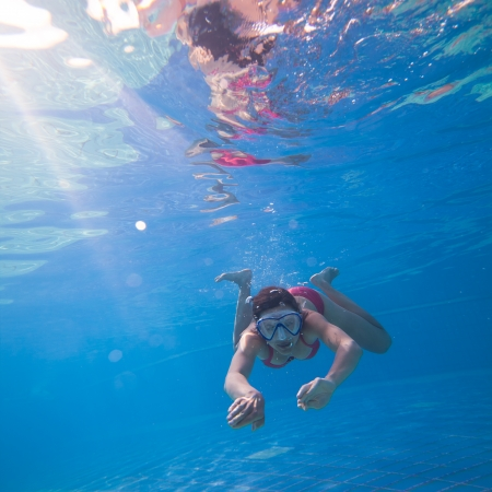 Underwater swimming: young woman swimming underwater in a pool, wearing a diving mask photo