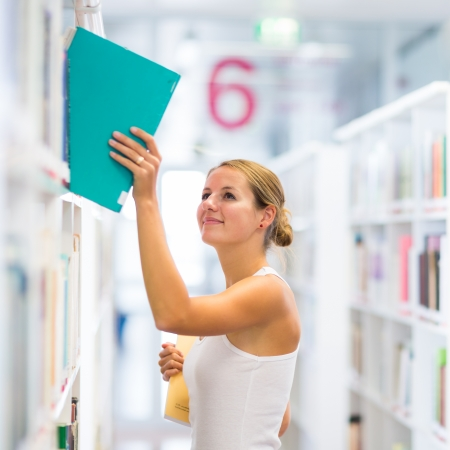 university choice: Pretty young college student in a library (shallow DOF; color toned image)