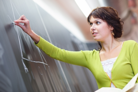 female teacher: Pretty young elementary schoolcollege teacher writing on the chalkboardblackboard during a math class