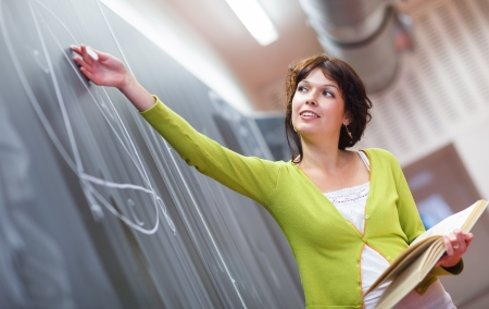 Pretty young elementary schoolcollege teacher writing on the chalkboardblackboard during a math class (color toned image; shallow DOF)