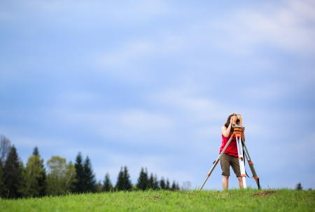 leveling: Young land surveyor at work