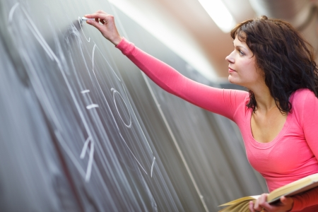 Pretty young elementary school/college teacher writing on the chalkboard/blackboard during a chemistry class (color toned image; shallow DOF) class (color toned image; shallow DOF) Stock Photo - 15284448