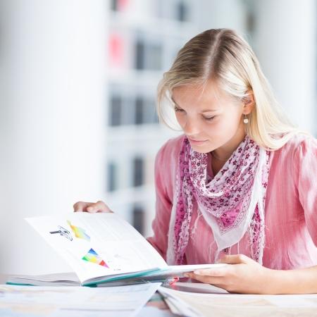 en la biblioteca - bastante estudiante femenino con los libros de trabajo en una biblioteca de la escuela secundaria