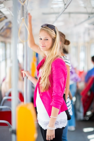 Pretty, young woman on a streetcartramway, during her commute to work (color toned image; shallow DOF) photo
