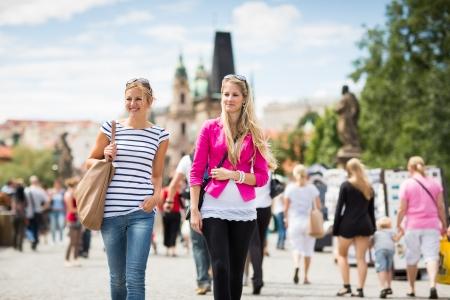 tour guide: Dos mujeres turistas paseando por el Puente de Carlos en Praga mientras turismo, la capital hist�rica de la Rep�blica Checa (imagen a color entonado, someras DOF) Foto de archivo