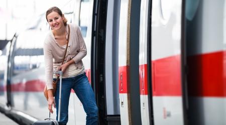 arrival departure board: Pretty young woman boarding a train Stock Photo