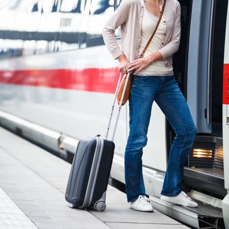 baggage train: Pretty young woman boarding a train Stock Photo