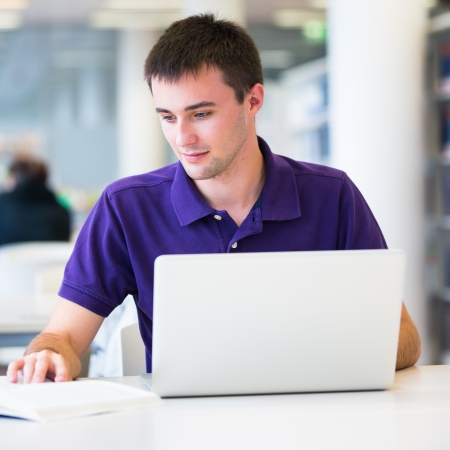 Handsome college student using his laptop computer in the campus common area/high school study room Stock Photo - 15284235