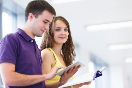 2 persons only: Two college students in library, reading books, using tablet computer Stock Photo