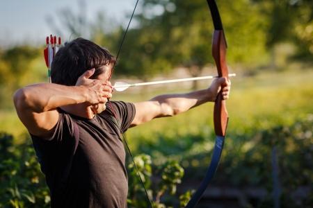 arco y flecha: Joven arquero entrenamiento con el arco