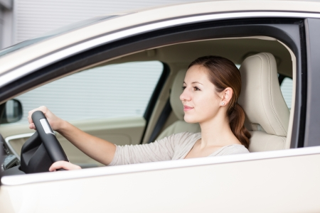 woman driving car: Pretty young woman driving her new car Stock Photo