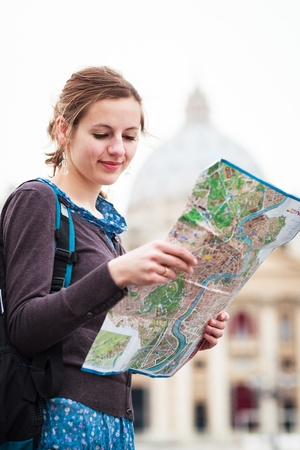 travel guide: Pretty young female tourist studying a map at St. Peters square in the Vatican City in Rome