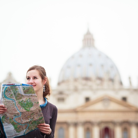 tourist guide: Pretty young female tourist studying a map at St  Peter