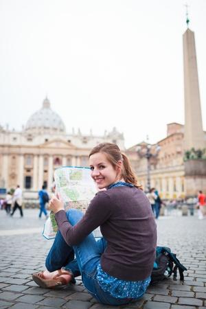 Travel Backpack: Turista femenino bastante joven estudiando un mapa de San Pedro Foto de archivo