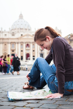 Pretty young female tourist studying a map at St  Peter Stock Photo - 15284349