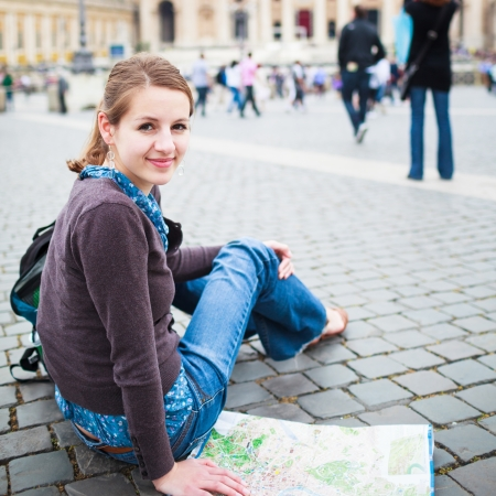 st peter s basilica: Pretty young female tourist studying a map at St  Peter