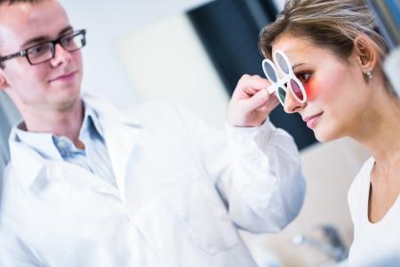 examen de la vista: Concepto de Optometría - mujer bastante joven que hace sus ojos sean examinados por un oftalmólogo Foto de archivo