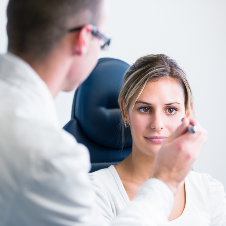 examined: optometry concept - pretty young woman having her eyes examined by an eye doctor