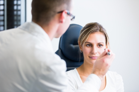 optometry concept - pretty young woman having her eyes examined by an eye doctor photo